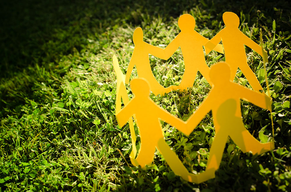 Closeup of a ring of yellow paper-chain people standing in the grass