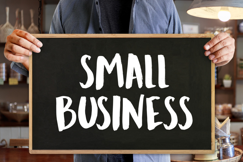 hands holding a sign that says Small Business